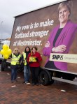 Dr Philippa Whitford with two local SNP team members standing beside the SNP Campaign Ad Trailer in Irvine