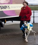 Dr Philippa Whitford walking a slatire clad dog with SNP badge round it's neck