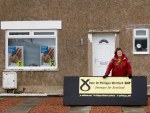 Dr Philippa Whitford standing outside a house in Prestwick that is displaying SNP posters.