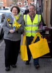 Dr Philippa Whitford walking with team member who is carrying some yellow SNP bags