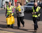 Dr Philippa Whitford walking with team member and Hans. Team mamber is carrying some yellow SNP bags