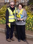 Dr Philippa Whitford with Hans standing beside spring flowers in Prestwick
