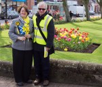 Dr Philippa Whitford with Hans standing in front of spring flowers in Prestwick