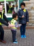 Adult in SNP hi-viz vest and one child in hi-viz vest with another looking on