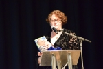 Philippa Whitford at podium about to announce the draw for the signed and certificated Alex Salmond book