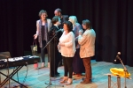 Acts on stage receiving gifts from Philippa Whitford at end of fundraising event