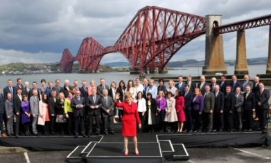 Dr Philippa Whitford at South Queensferry with the  other 55 SNP MPs and the First Minister.  Forth railway Bridge in background.
