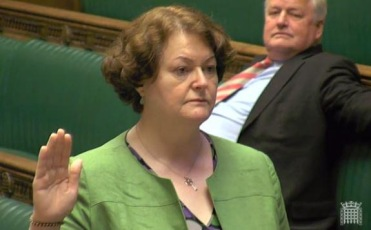 Dr Philippa Whitford being sworn in as an MP in the Hose of Commons.  Tory MP on benches behind her.